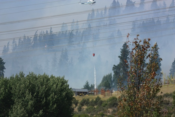 helicopter dropping water near building