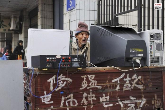 Chengdu, Sichuan, 69-year-old Hu Kaiyuan sitting on his workbench repairing an old computer