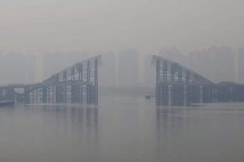 Buildings are seen through smog behind an unfinished bridge near the Yujiapu financial centre, in Tianjin, China February 22, 2016. REUTERS/Jason Lee/File Photo