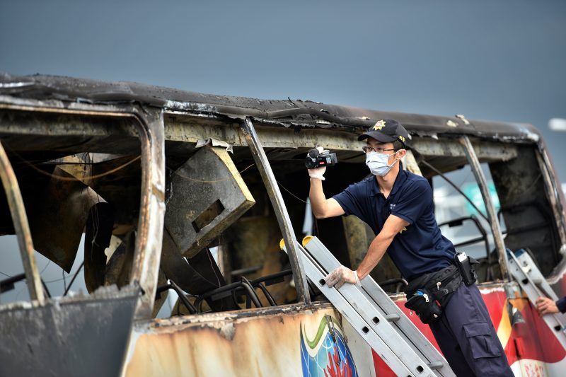 A policeman films the wreckage of a bus that crashed en route to Taoyuan airport, just south of the capital Taipei July 19, 2016. REUTERS/A-Kun Li