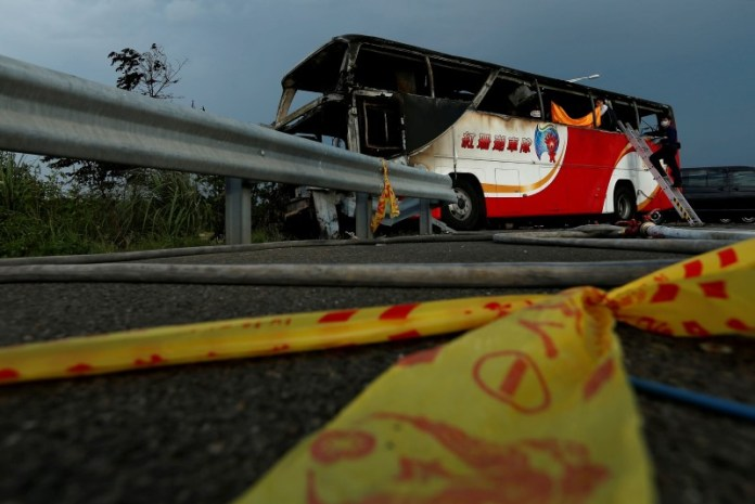 Police work around the wreckage of a bus that crashed en route to Taoyuan airport, just south of the capital Taipei, Taiwan July 19, 2016. REUTERS/Tyrone Siu