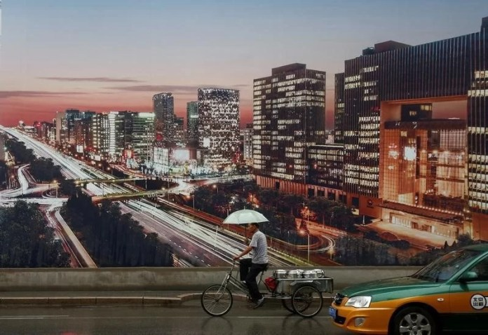 A man rides a tricycle past an advertising poster showing a night-time city view in Beijing,