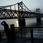 A man watches the sun rise behind the bridge over Yalu River that connects China's Dandong, Liaoning province, and North Korea's Sinuiju, September 11, 2016. REUTERS/Thomas Peter