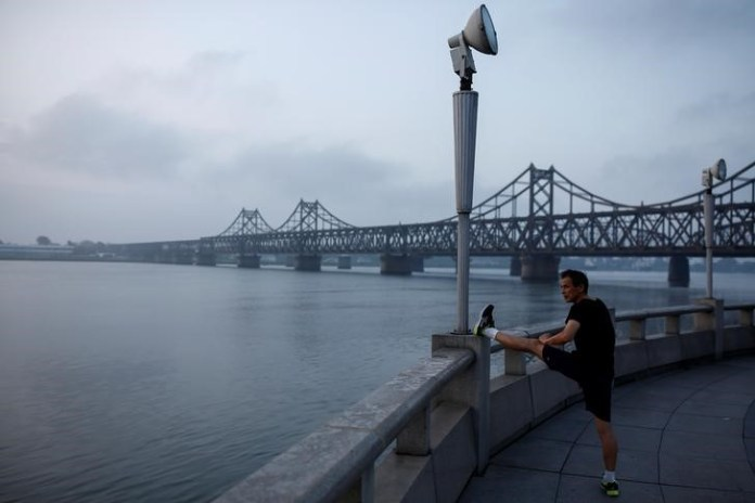 A man stretches at the embankment of the Yalu River in front of the bridge that connects China's Dandong, Liaoning province, and North Korea's Sinuiju, September 11, 2016. REUTERS/Thomas Peter