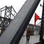 A woman walks across the destroyed bridge over the Yalu River that once linked North Korea's Sinuiju and Dandong in China's Liaoning province, September 10, 2016.  REUTERS/Thomas Peter