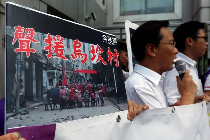 """Protesters demonstrate with a placard which reads """"Support Wukan village"""" outside China Liaison Office in Hong Kong, China September 14, 2016.      REUTERS/Bobby Yip"""