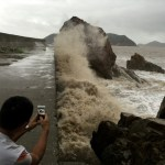 A man records waves whipping the shore before Typhoon Meranti makes a landfall on southeastern China, in Wenling