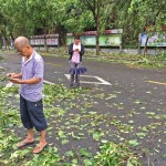People take pictures with mobile phones on a street after Typhoon Meranti swept through Xiamen