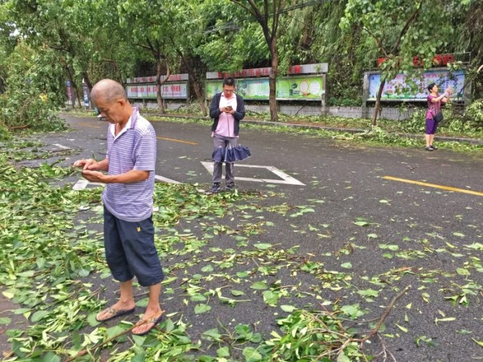 People take pictures with mobile phones on a street after Typhoon Meranti swept through Xiamen, Fujian province, China, September 15, 2016. REUTERS/Stringer