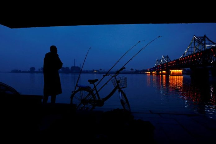 A man looks across Yalu River towards North Korea as he stands next to the bridge that connects China's Dandong, Liaoning province and North Korea's Sinuiju, September 10, 2016.  REUTERS/Thomas Peter/File Photo