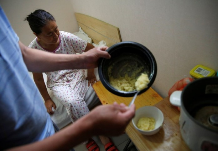 Liu serves breakfast for his wife, Wang, in their room at the accommodation where some patients and their family members stay while seeking medical treatments in Beijing, China, June 23, 2016. REUTERS/Kim Kyung-Hoon