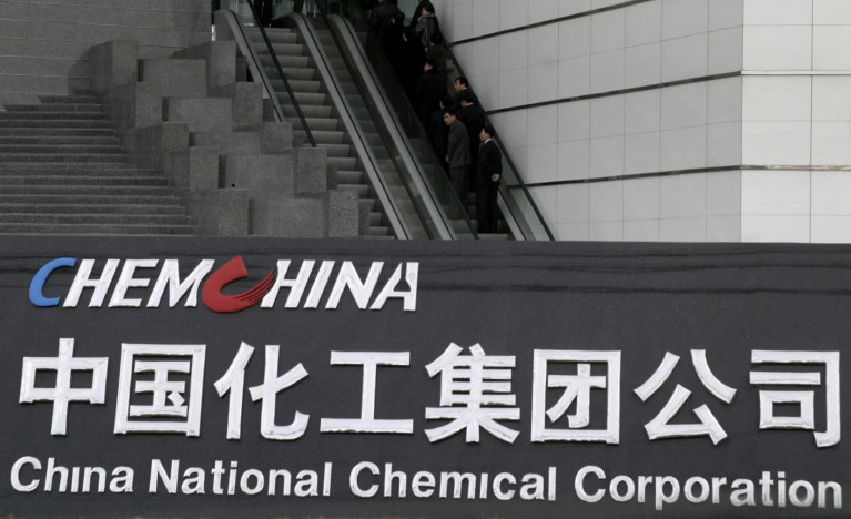 People use an escalator outside the headquarters of ChemChina (China National Chemical Corporation) in Beijing, China