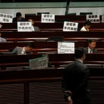 """Pro-democracy protesters display placards which read """"Andrew Leung does not represent me"""", referring to the Legislative Council president, during a demonstration inside the council's chamber in Hong Kong"""