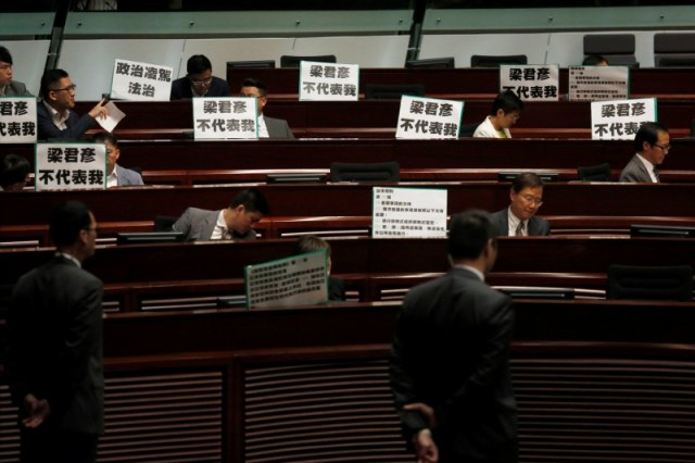"Pro-democracy protesters display placards which read ""Andrew Leung does not represent me"", referring to the Legislative Council president, during a demonstration inside the council's chamber in Hong Kong, China October 26, 2016.  REUTERS/Bobby Yip"