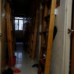 """A corridor with ladders is seen inside a flat filled with partitioned units, or """"coffin units"""", in Hong Kong"""