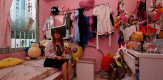 Manman Luk poses inside her sub-divided unit in Hong Kong
