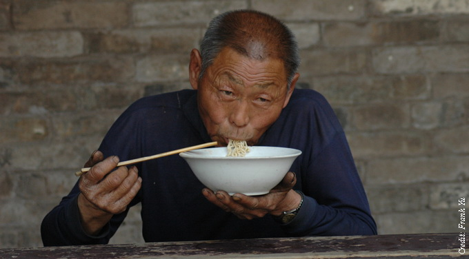 chinese man eat noodles