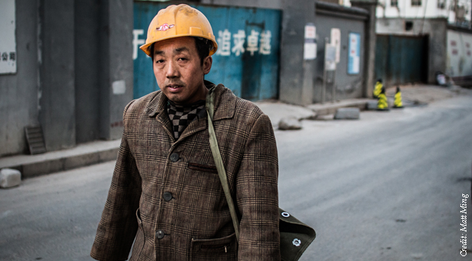 migrant worker walking hard hat