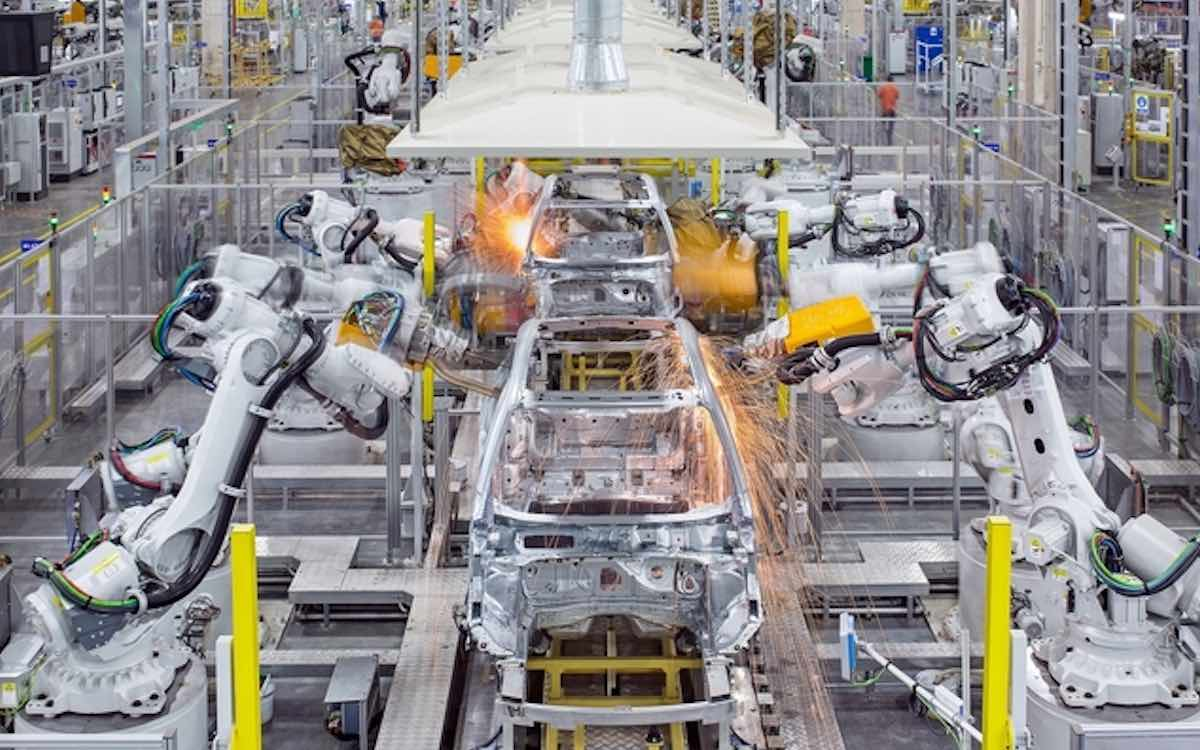 The photo shows robots moving into action at a high-tech Volvo plant in China. Manufacturing activity slowed in February.