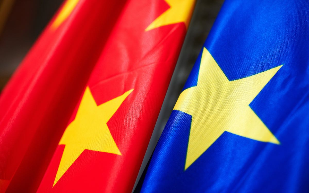The image shows Chinese and European Union flags merged in red and blue. China's investment deal with the EU has caused controversy.
