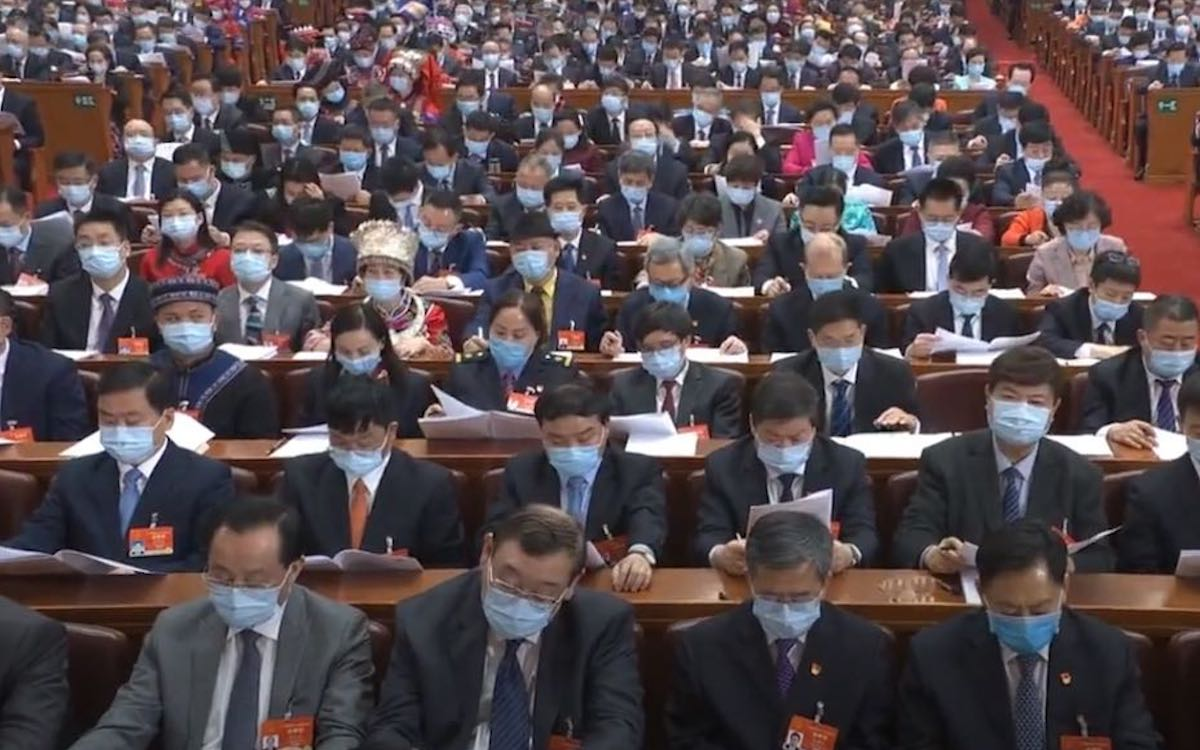 The image shows Communist Party delegates at the National People's Congress. Premier Li Keqiang delivered his work report on Friday.