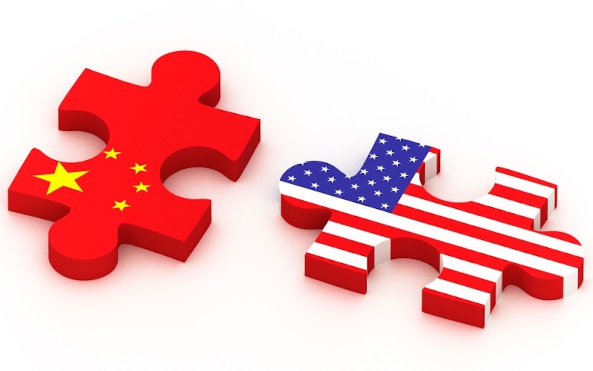 The image shows two pieces from a jigsaw puzzle covered in Chinese and US flags. Solving the puzzle between the US and China will prove tricky.