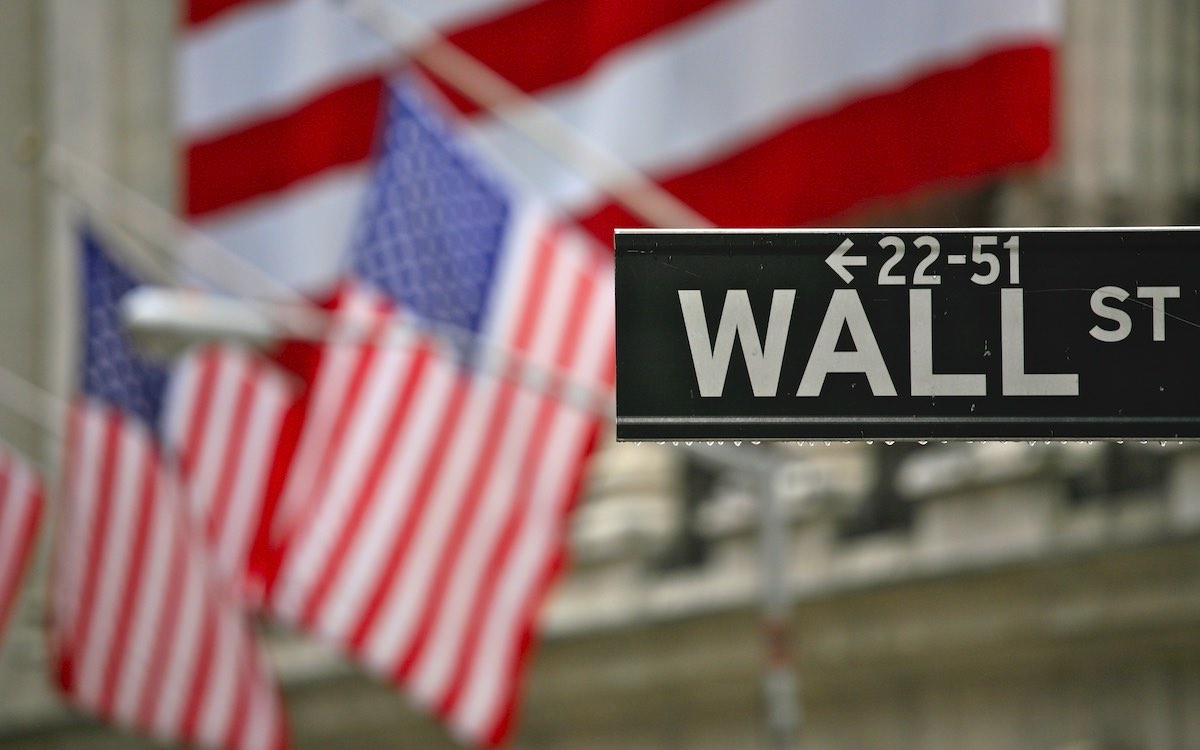 The photo shows the Wall Street sign against a backdrop of American flags. Chinese companies face the threat of delisting in the US.