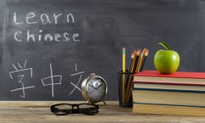 Student learning Chinese with books, pencils, clock, reading glasses and an apple in front of chalkboard with Mandarin text.