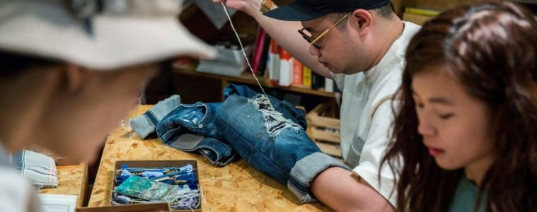 "This picture taken on September 9, 2018 shows a participant at a ""Fashion Clinic"" workshop mending his old jeans. - Despite Hong Kong's reputation for rampant consumerism, a nascent movement against fast fashion is taking root in the city, with clothes-mending workshops and pop-up swaps growing in popularity, and designers parading recycled fabrics on the catwalk. (Photo by Isaac LAWRENCE / AFP) / TO GO WITH HongKong-fashion-environment-textile-lifestyle, FEATURE by Yan ZHAO (Photo credit should read ISAAC LAWRENCE/AFP/Getty Images)"