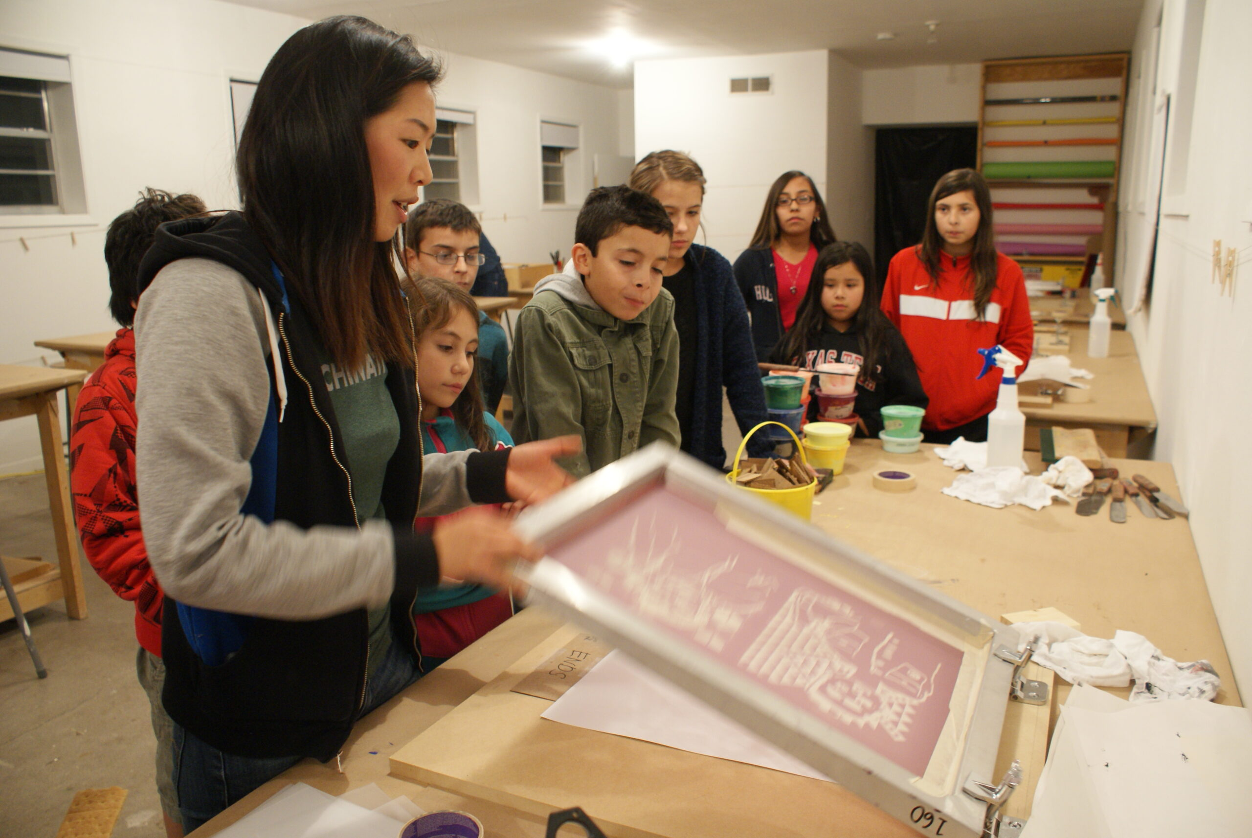 Education intern leading a student workshop in screen printing.