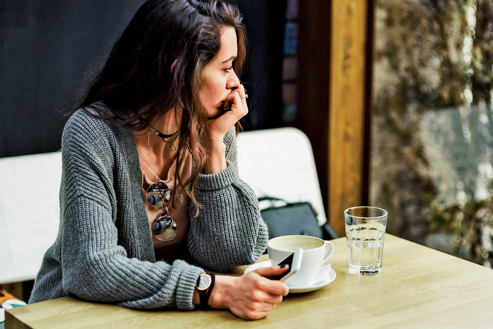Woman sitting alone, having coffee and texting on her mobile phone