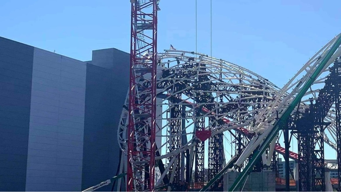 Tron Coaster reaches its tallest point crews top it off with an American Flag