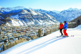 Two girls skiing with a city view