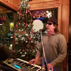 a photo of chip on stage at River Street Tavern, christmas of 2018. He is standing behind his keyboard with his guitar strapped on and is singing.