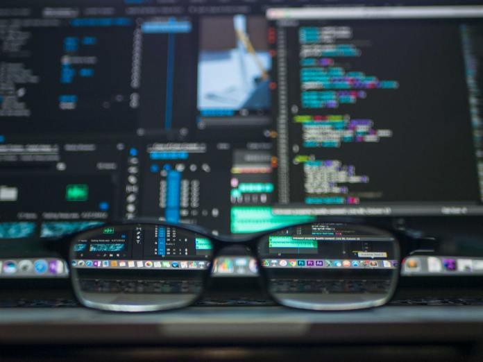 a pair of glasses facing a screen full of code
