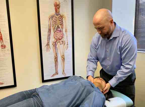 Dr. Michael White, Accident Chiropractor in Miami Lakes performing a chiropractic adjustment.