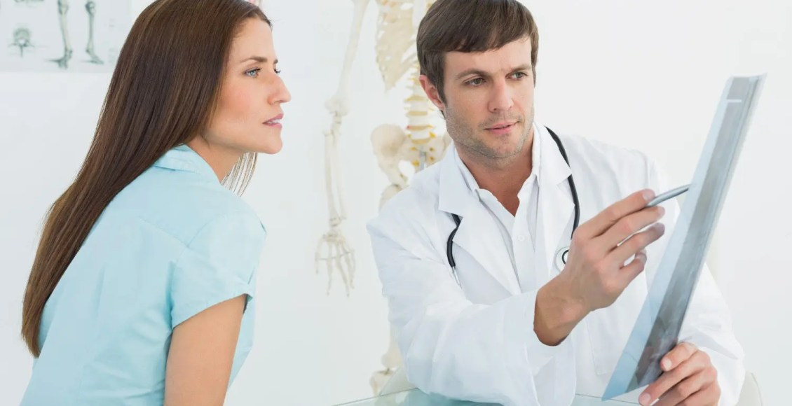 chiropractor discusses x-ray with patient