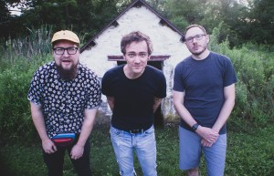 Patrick, Dan, and Warren looking at the camera and standing in front of an old spring house in a field