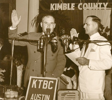 Photograph of Governor Coke Stevenson speaking into a radio microphone. A man stands next to him, and both of them have their right hands in the air. [Governor Coke Stevenson], photograph, 1941; (https://texashistory.unt.edu/ark:/67531/metapth354799/m1/1/?q=Governor%20Coke%20Stevenson: accessed February 13, 2020), University of North Texas Libraries, The Portal to Texas History, https://texashistory.unt.edu; crediting McAllen Public Library.