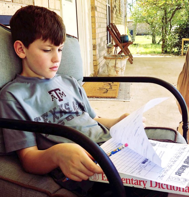 Meridian ISD second grader Greyson Gilbert does a reading/spelling assignment on the porch. Photo by LEIGH GILBERT of Loveleigh Photography