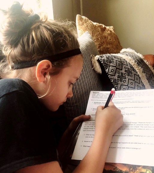 Meridian ISD fourth grader Daylee Gilbert finds the couch to be a perfect spot to do her distance learning school work. Photo by LEIGH GILBERT of Loveleigh Photography