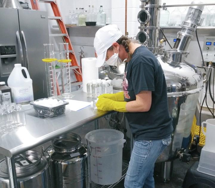 RCD's distiller Jennifer Davis labels an eight-ounce bottle of medical-grade hand sanitizer.