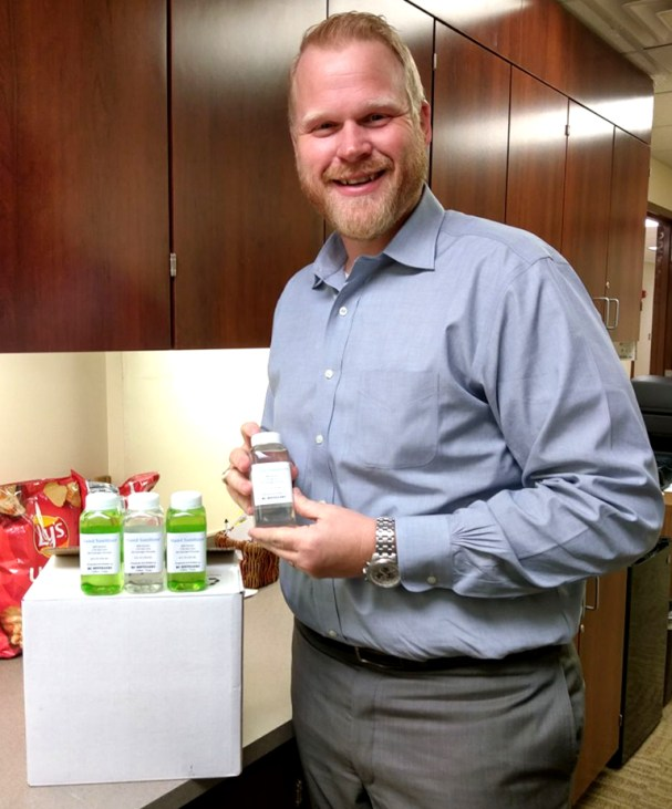 Goodall-Witcher Healthcare's CEO Adam Willmann accepts a donated 20-bottle box of medical grade, 80-proof hand sanitizer from Red Caboose Distillery last week.
