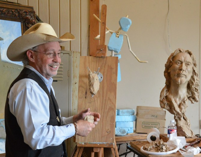 Bruce Greene gives a demonstration of how he works to a group of art patrons from Arizona.
