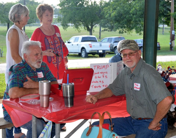 Volunteers John and Mary Susan Kennedy selling dinner and merchandise tickets – to Paul Hardcastle in this case - at the Bosque County Republican Club Party in the Park event June 16.