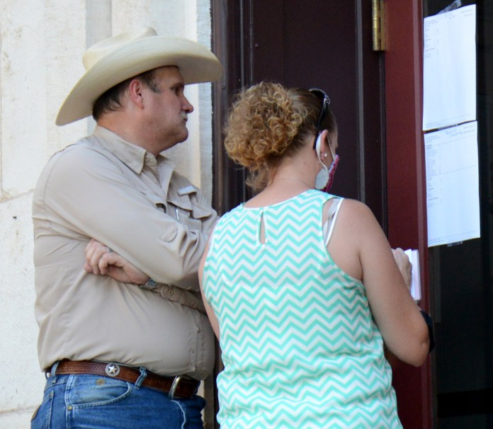 Bosque County Chief Deputy Clint Pullin and his wife Brandy review voting precinct results at the Bosque County Courthouse during the Runoff Election July 14.