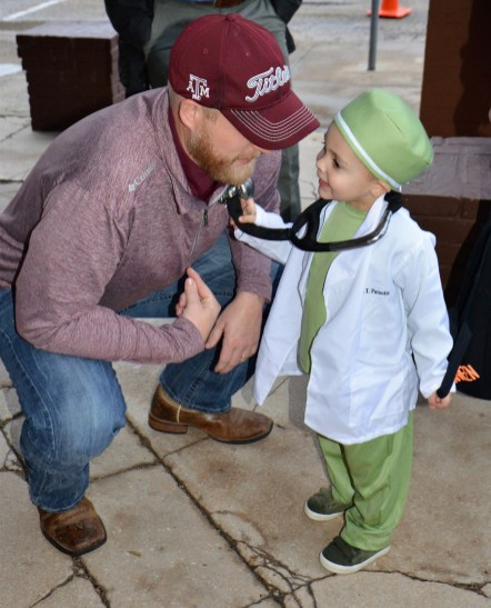 Goodall-Witcher Healthcare CEO Adam Willmann gets a check-up from an aspiring physician during the annual Halloween on Main Street event in Clifton.