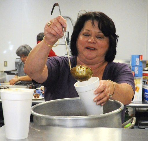 Former Meridian Public Library Board President Teresa McMahon ladles out chili during a Fall Chili Supper.