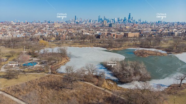 Aerial View Above Frozen Humboldt Park Lagoon with Chicago Skyline