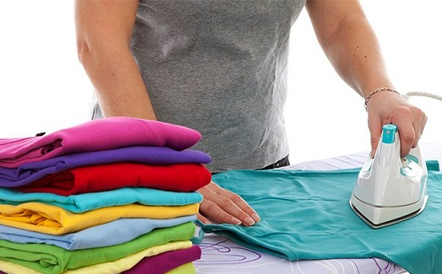 Woman strokes multicolored underwear on ironing board